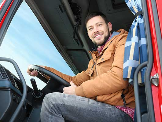 truck driver sitting in a truck and smiling